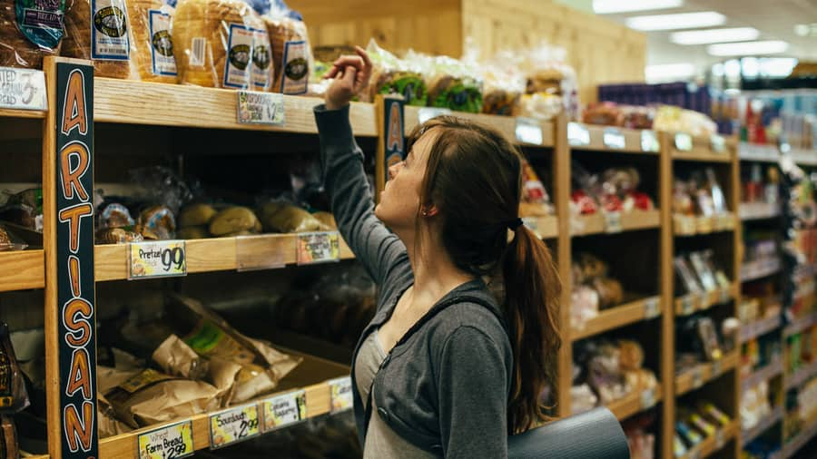 A young woman chooses from a selection of artisan breads at the grocery store
