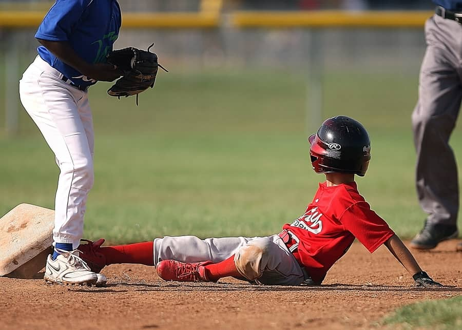Little league ballplayer looks to the umpire for a ruling after sliding into second base. - Houston Texas